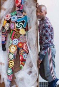 L'artiste Nick Cave posant avec l'un de ses Soundsuits.