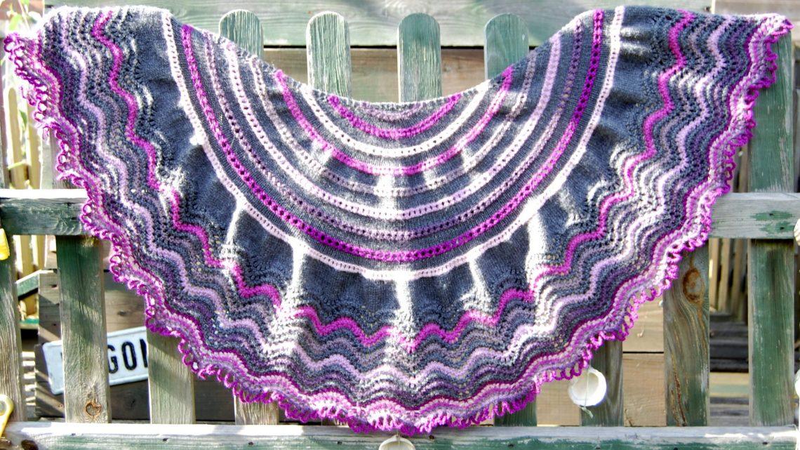 audrey shawl in paars en grijs hangend aan een hek door studio paars