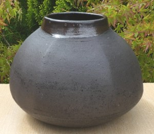 JL9 - Janet Leach black stoneware 6 sided cut vase. Personal and St. Ives seal. The height is 16.5 cm (6.5 inches) and the maximum diameter is 22.6 cm (8.9 inches). Price £625