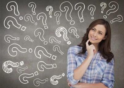 Donna davanti a una lavagna con sopra scritti dei punti interrogativi