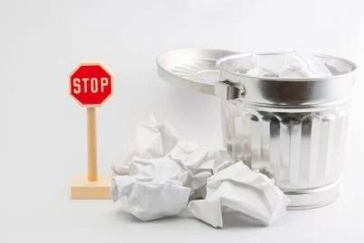 cartello di stop con bidoni spazzatura