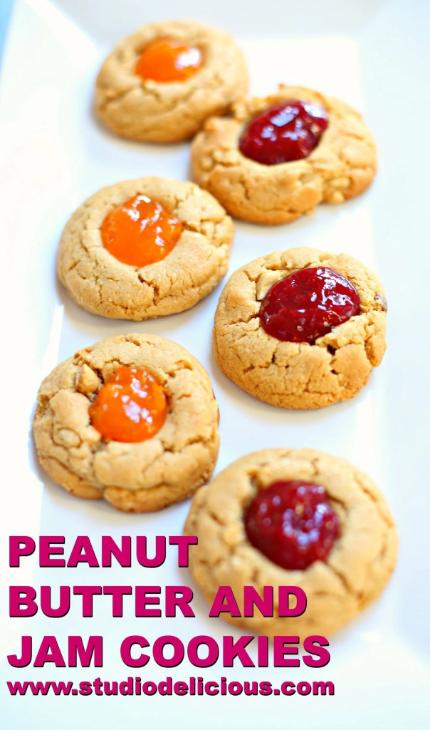 Peanut Butter and Jam Cookies on a white platter with cherry and apricot jam