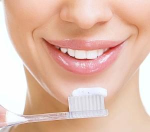Immagine di una ragazza con lo spazzolino da denti. Le gengive sanguinanti possono scaturire da uno spazzolamento troppo vigoroso
