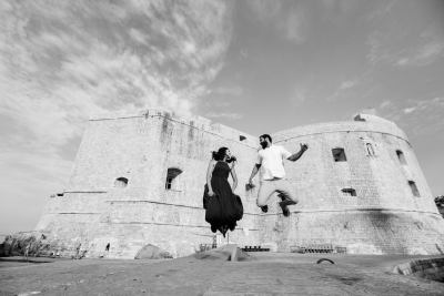 A couple is jumping in front of the Dubrovnik wedding photographer