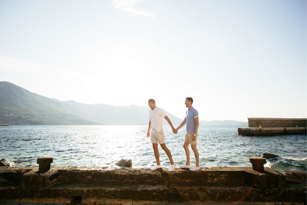 A gorgeous couple walking by the sea near Dubrovnik. Gay wedding in Dubrovnik.