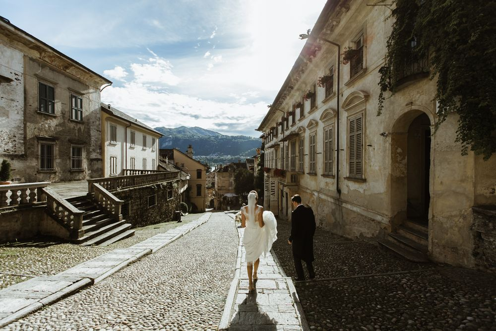Bride and groom on way to Piazza Motta in Orta during the Wedding photo session. Image by DTstudio Italy wedding photographer