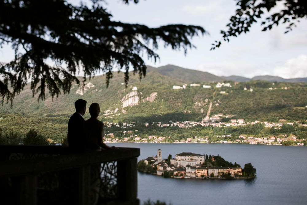 Bride and groom looking towards the San Giulio Island while their wedding weekend in Italy captured by © Tuscany Wedding Photographer