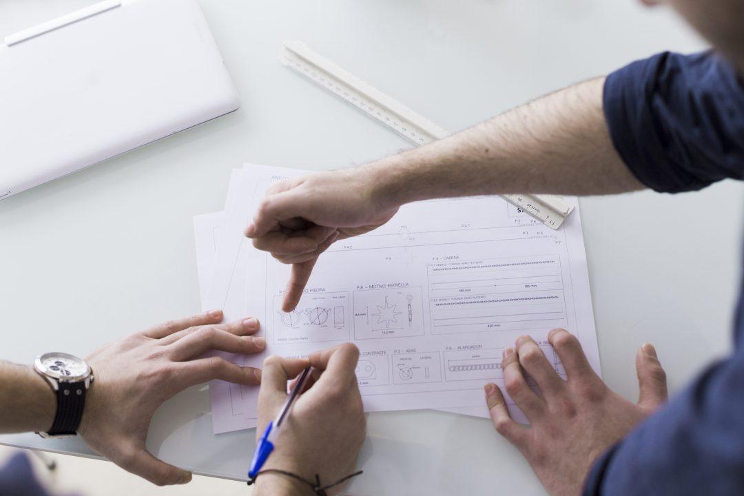 Mãos apontando as mudanças num relatório