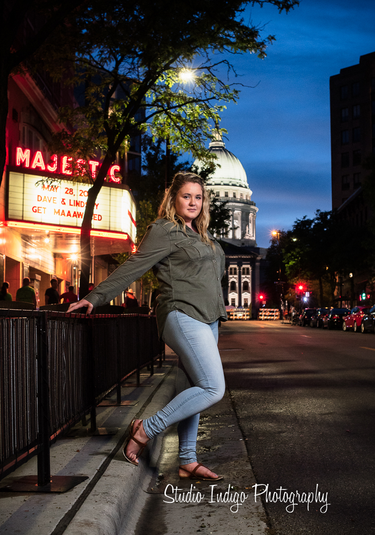 Madison West junior Allie under the Majestic theater marquee for her high school senior portrait.  Night time with cool light from the theater sign and the capital in the background.