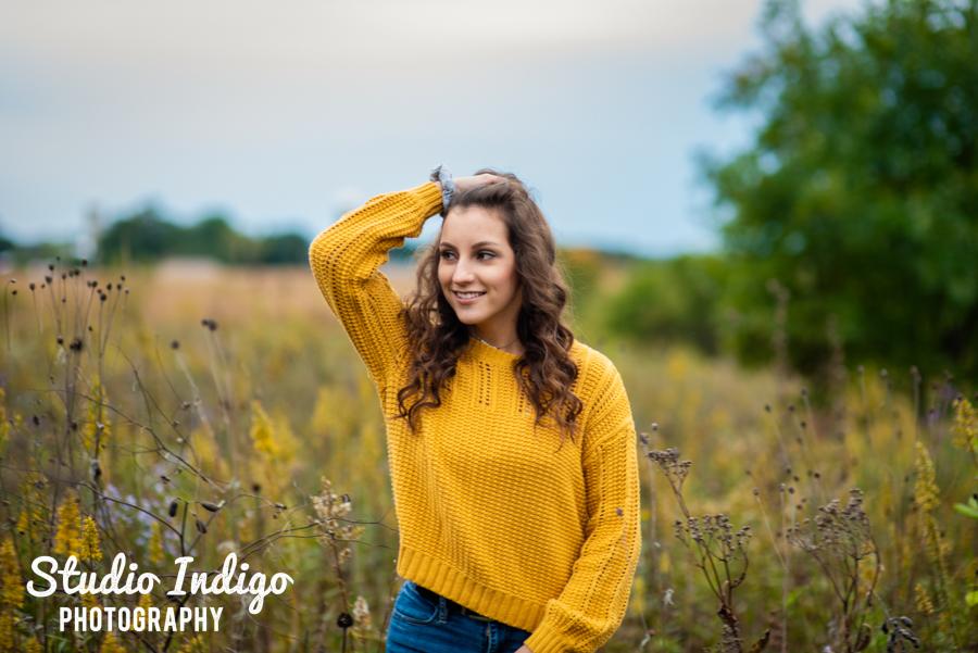 Candid portrait of high school senior girl walking through field of wildflowers