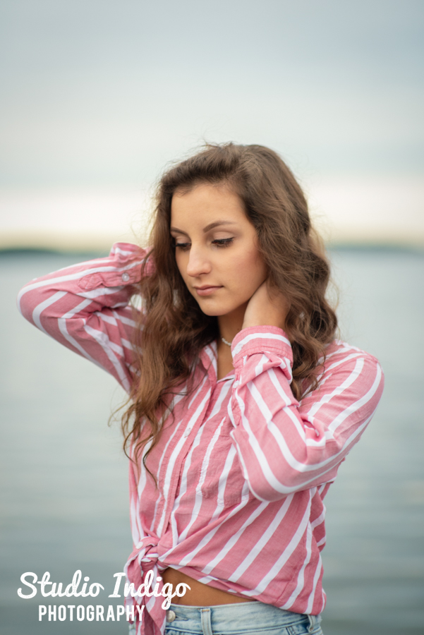 Portrait of high school senior  girl in a dramatic pose on a dock.