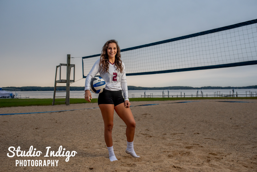 Portrait of high school senior girl in her volleyball uniform posing in front of sand volleyball court at dusk
