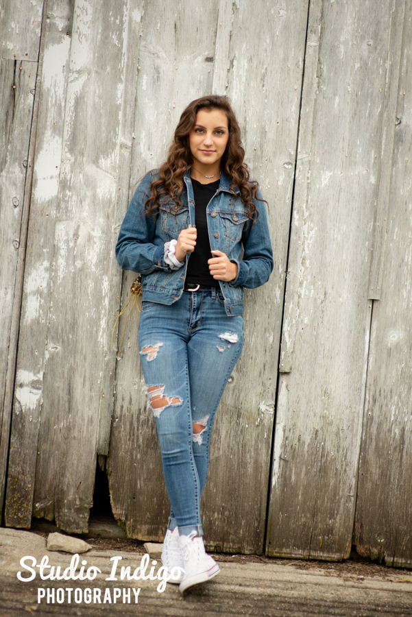 high school senior picture of girl in denim jacket and jeans leaning against a barn