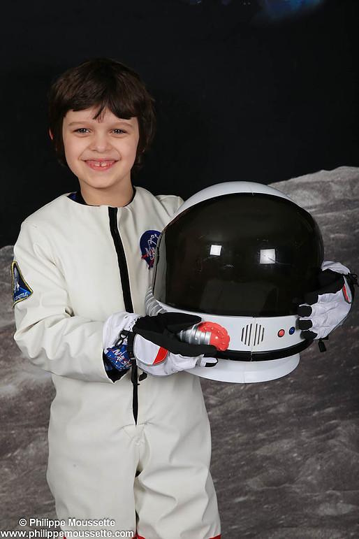 Garçon astronaute avec casque entre les mains