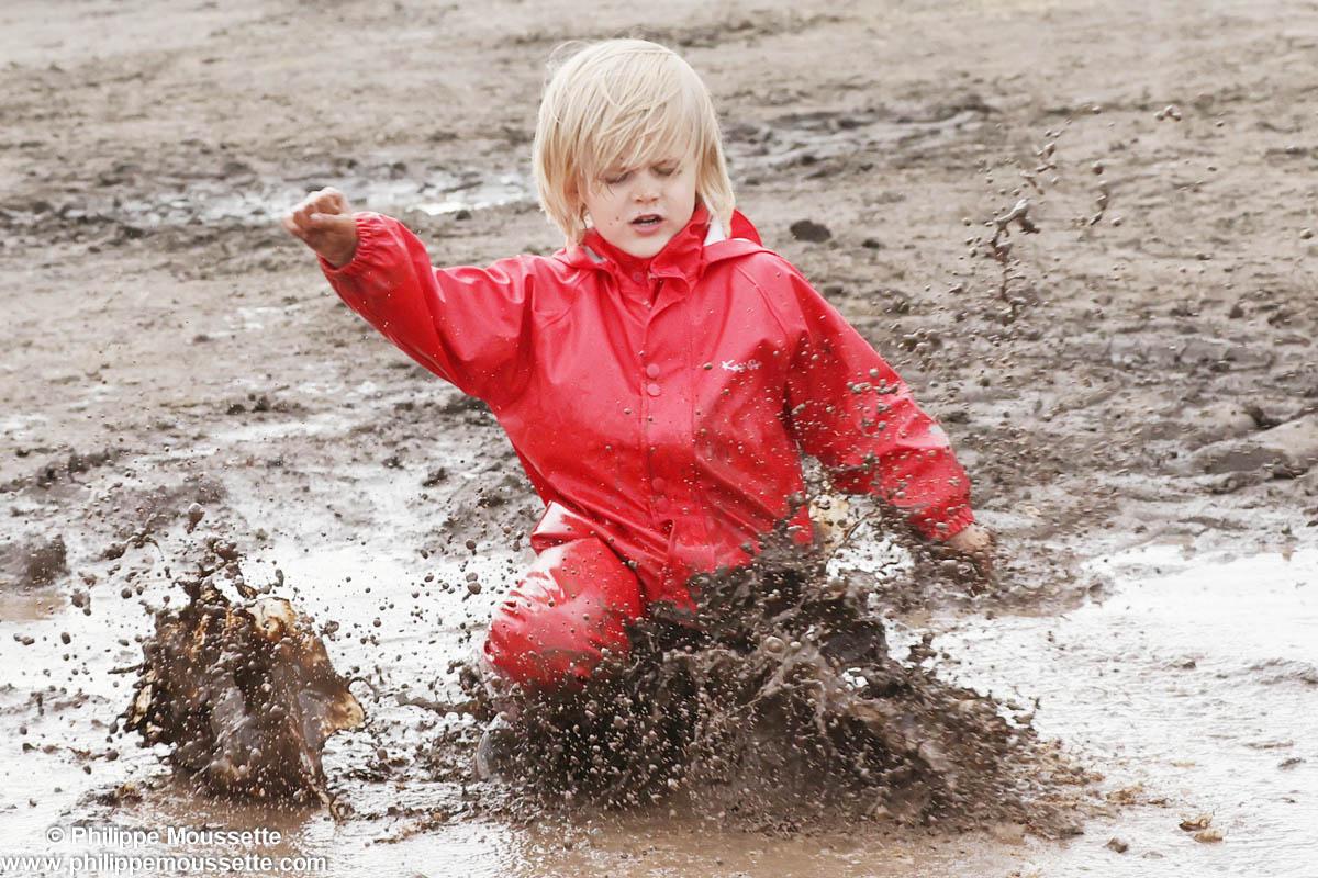 Garçon avec un imper rouge qui joue dans la boue