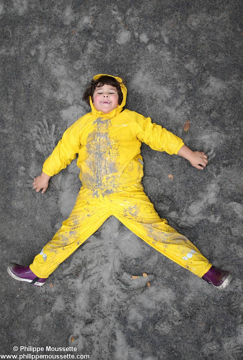 Fille avec un imper jaune qui fait l'étoile sur le sol