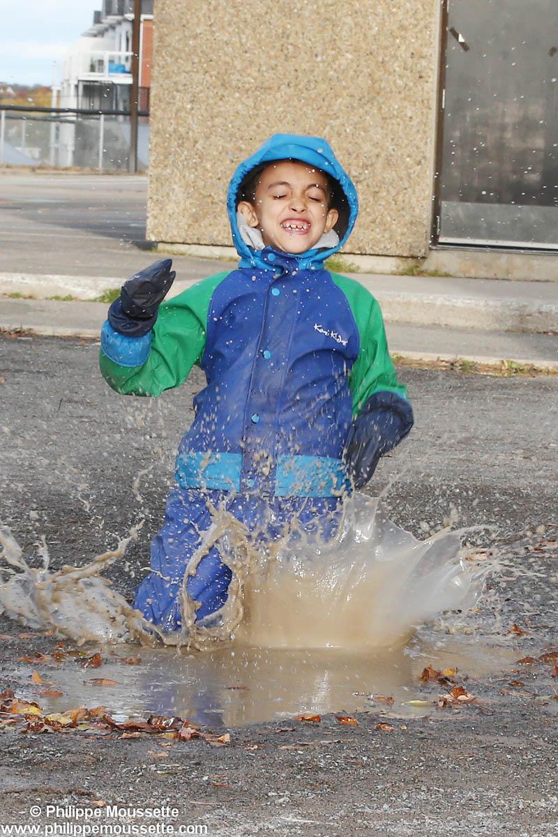 Enfant avec un imper qui joue dans l'eau