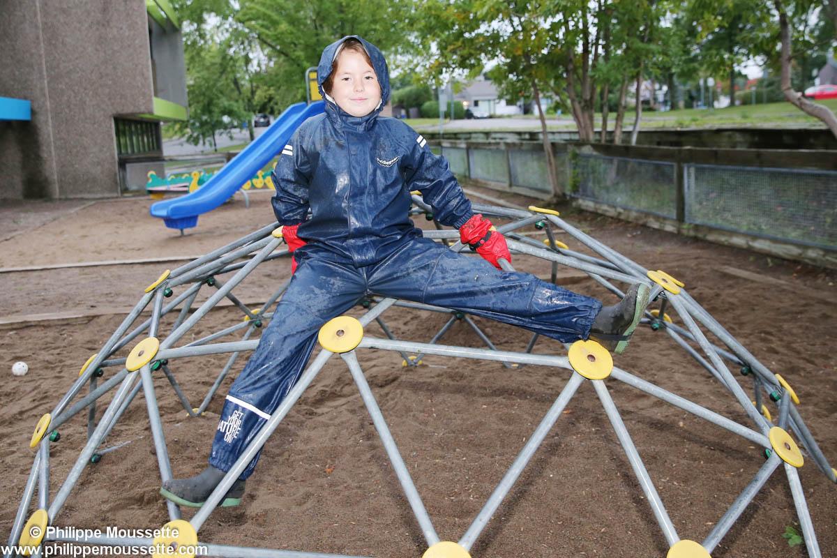 Enfant avec imper grimpé dans un jeu