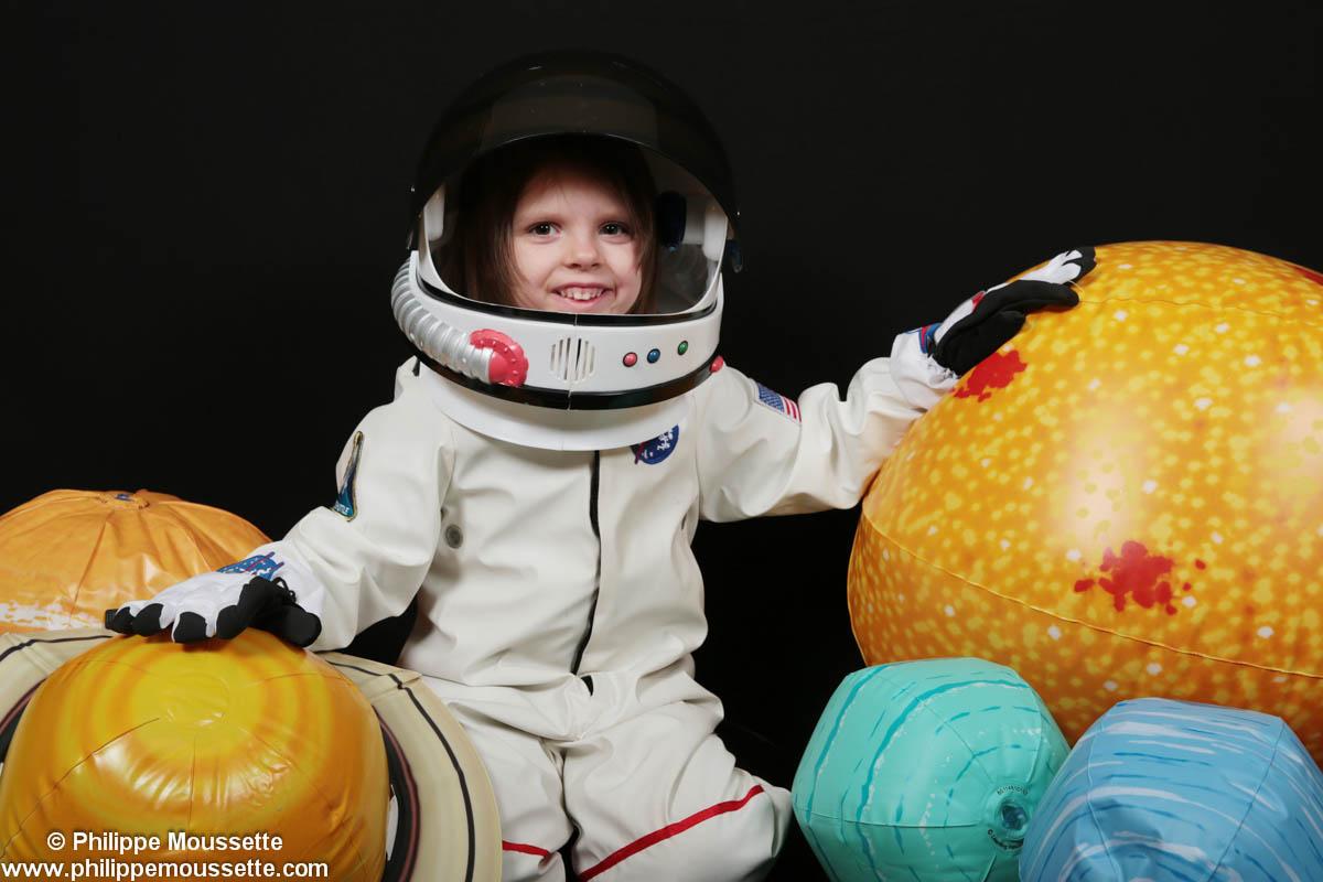 Garçon costumé en astronaute avec ballons en forme de planète