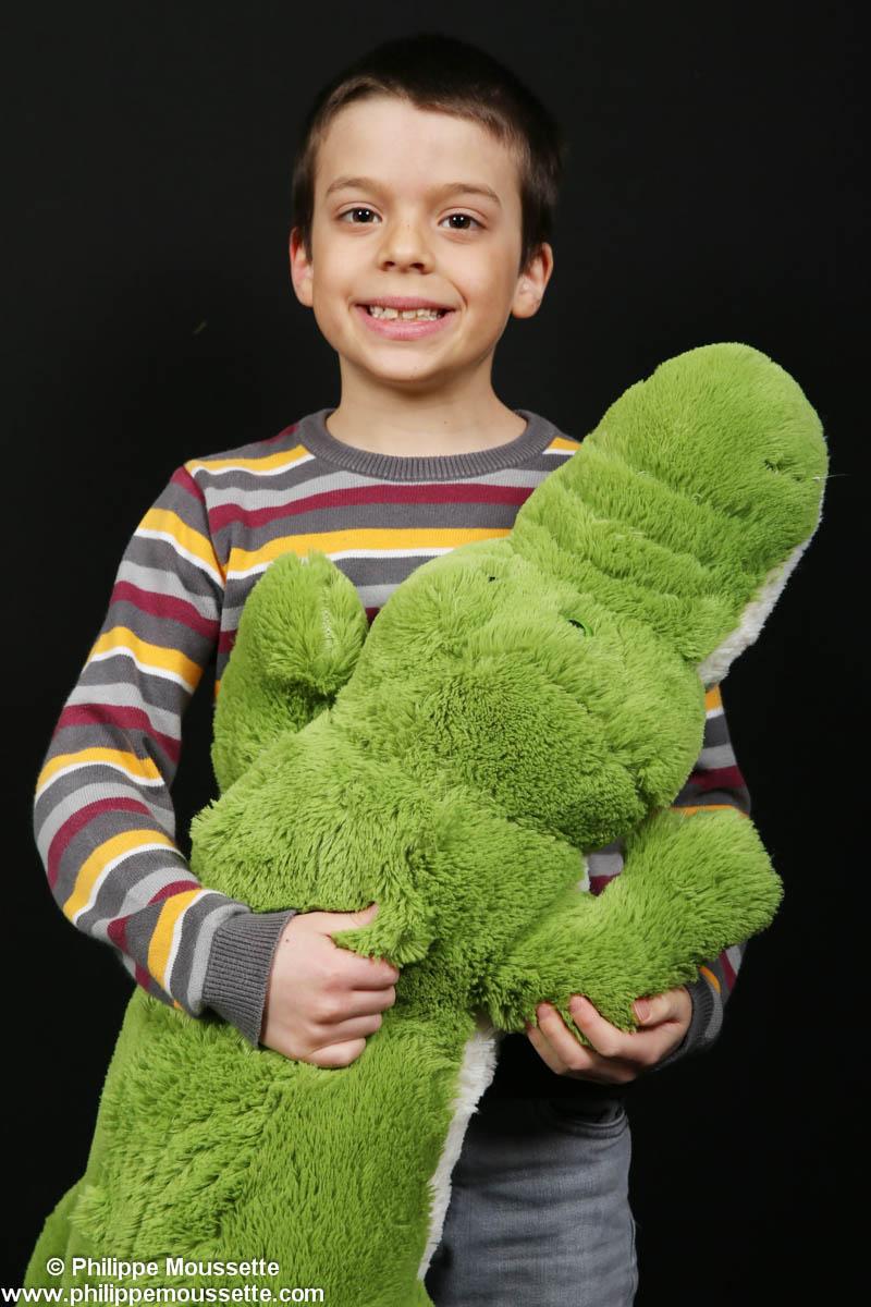 Garçon qui tient un toutou crocodile