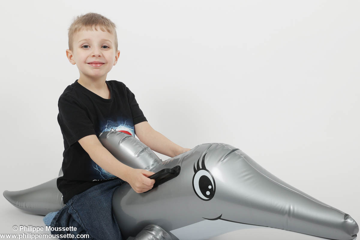 Enfant assis sur un dauphin gonflable
