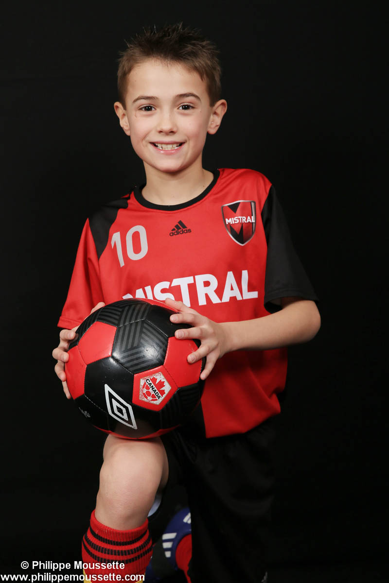 Jeune joueur de soccer avec son ballon sur le genou