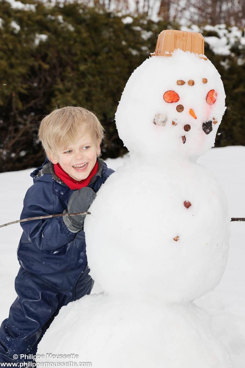 Garçon avec un bonhomme de neige