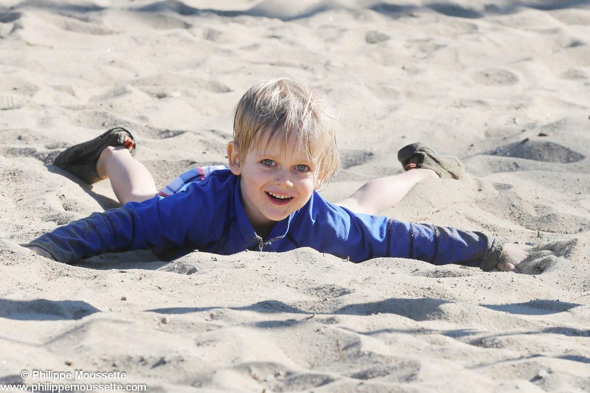 Enfant couché dans le sable