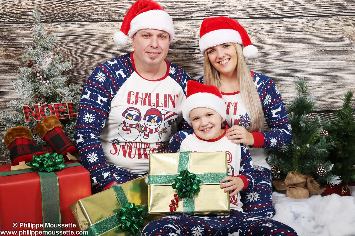Famille en pyjama dans un décor de Noël