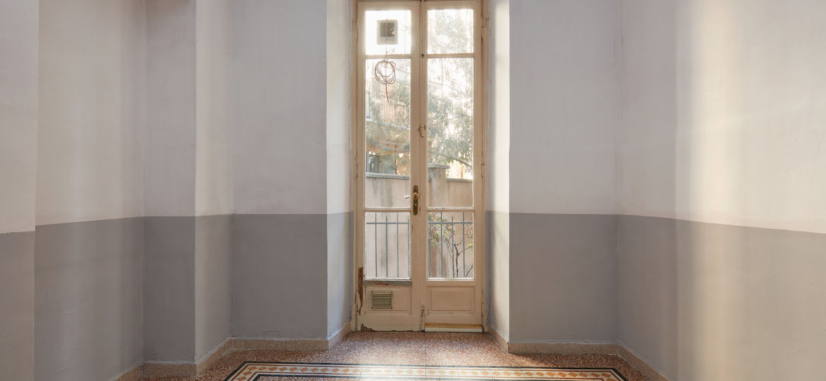 Empty room interior with tiled floor and window with balcony