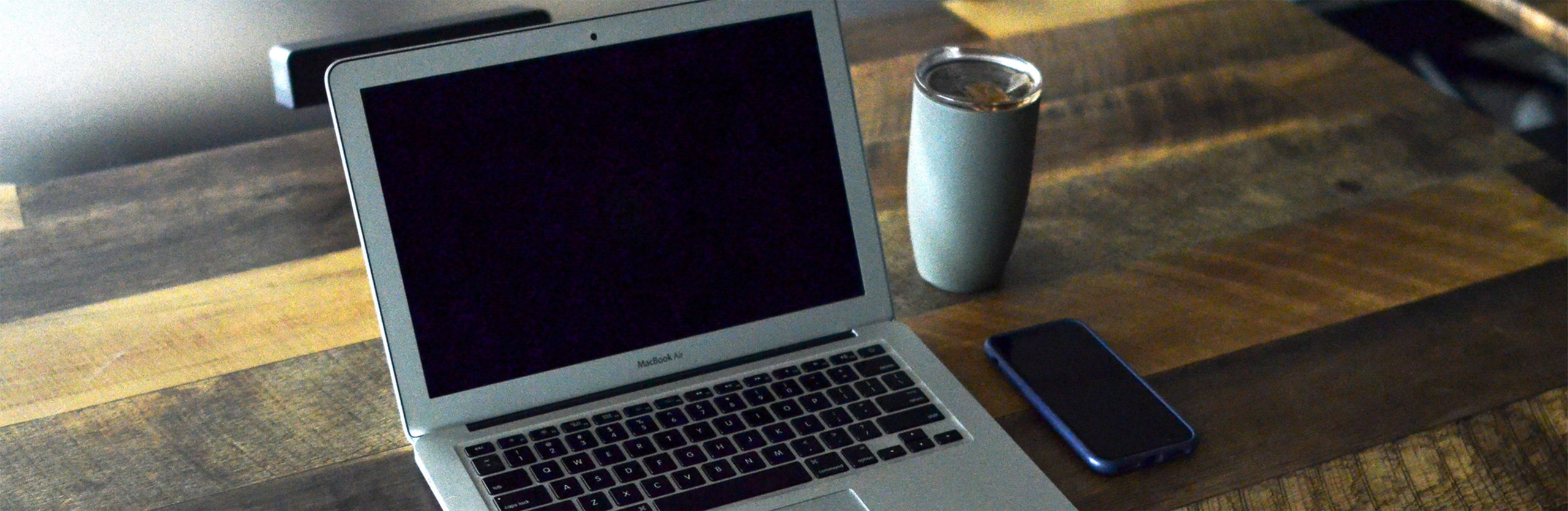 A laptop, smartphone, and coffee on the desk that's ready for a productive work day.