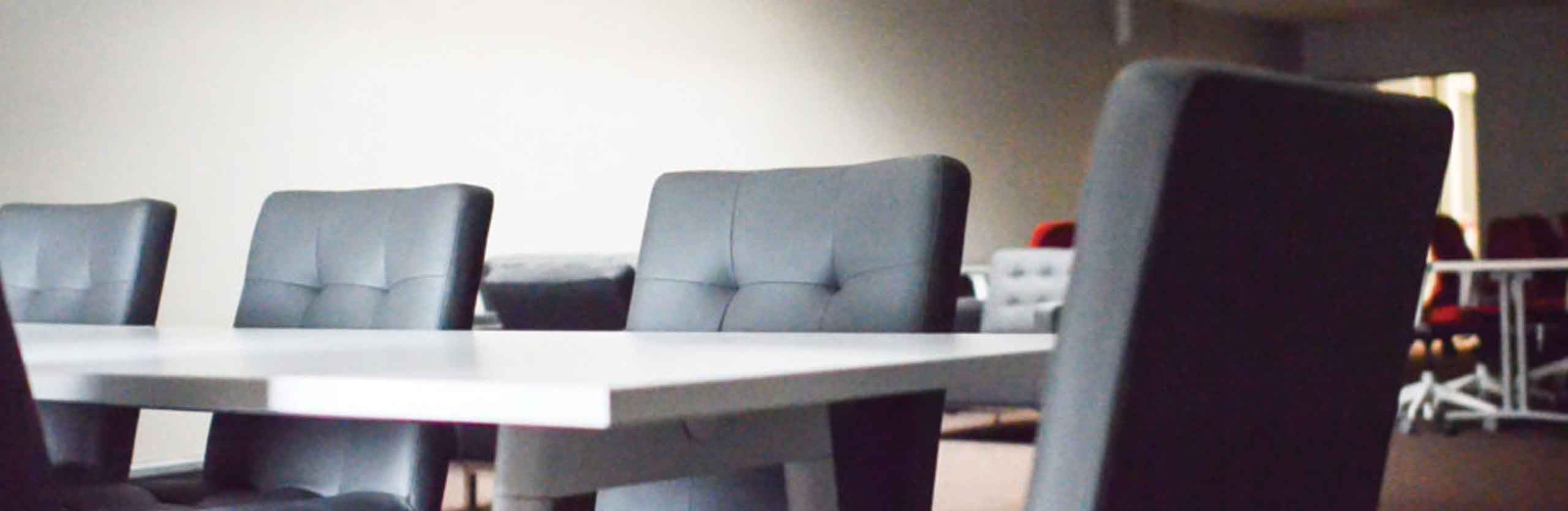 Modern grey couches sit in the shared coworking space of The Studio Coworking.