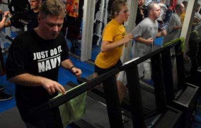 People running on treadmill at gym'