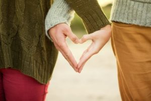 Couple holding hands to form heart
