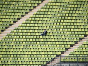 Person sitting alone in stadium