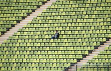 Person sitting alone in stadium