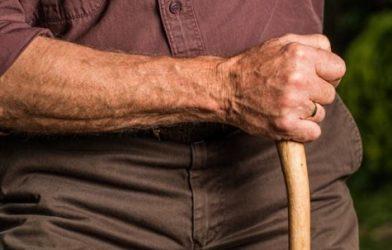 Older man holding cane or walking stick