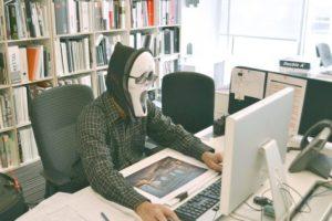 Man wearing Scream mask at office desk