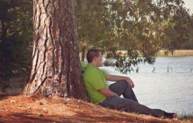 Man sitting alone next to a tree