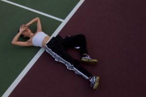 Woman lying on tennis court