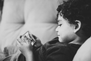Child laying on couch with phone