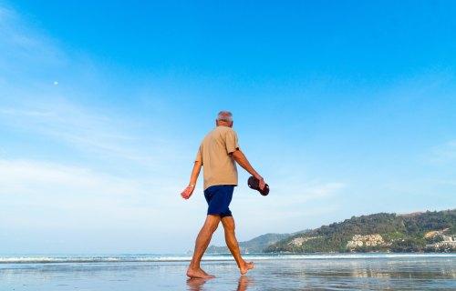 Older man walking on beach