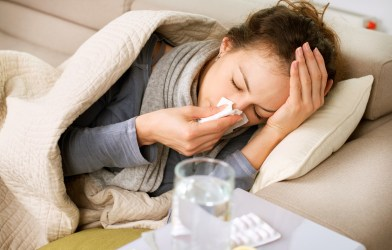 Sick woman blowing nose, has common cold and flu symptoms