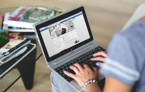 Woman looking at Facebook on laptop