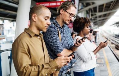 People staring at their smartphones on a subway platform