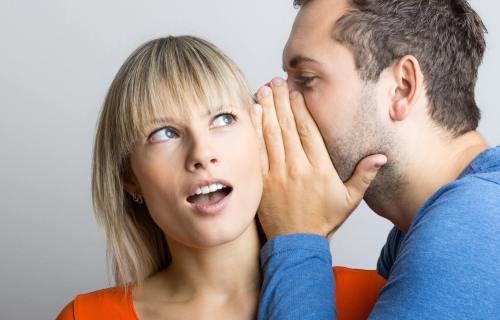 Man telling a woman a secret