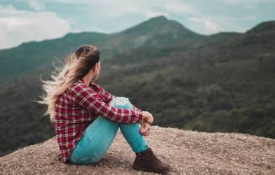 Woman sitting alone on a mountain