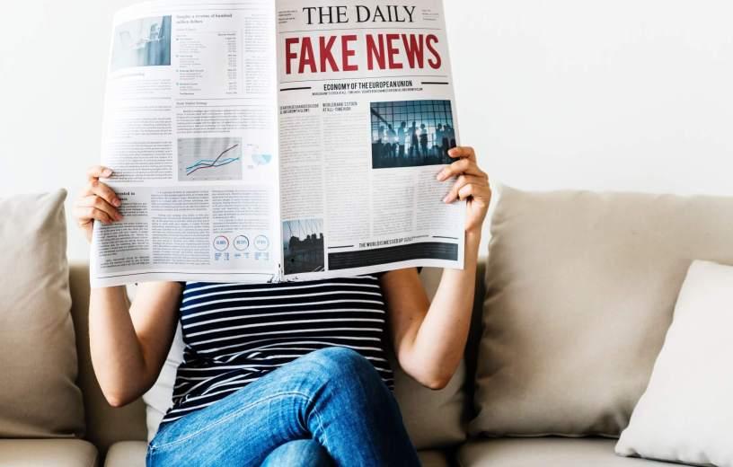 Woman reading 'Fake News' newspaper