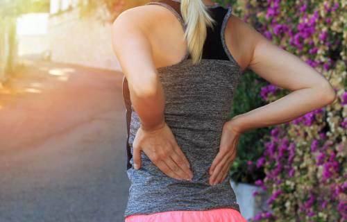 Runner applying acupressure for lower back pain