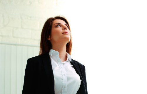 Business woman looking up at glass ceiling in office